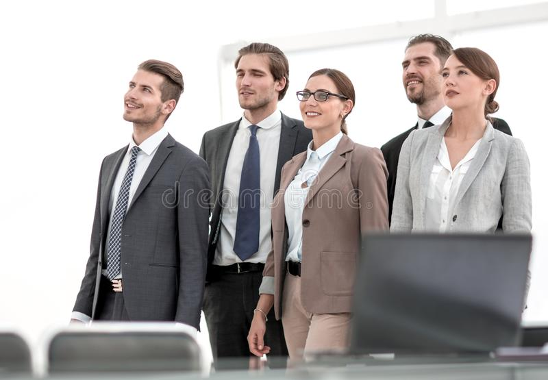 Grupo de empleados que se colocan cerca de la mesa fotos de archivo