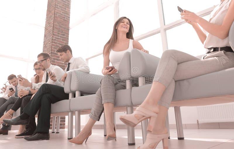 Grupo de empregados com os dispositivos que sentam-se no corredor do escritório foto de stock royalty free
