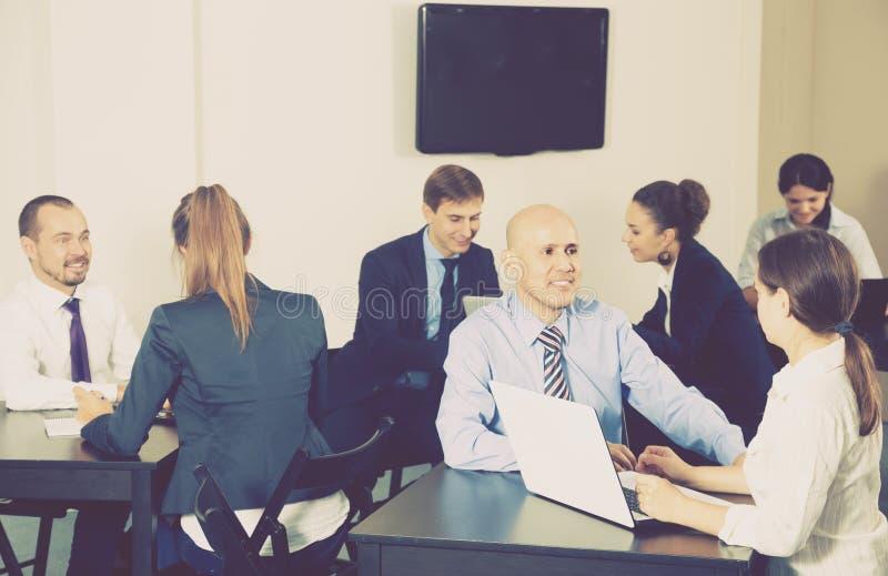 Grupo de empregados com os portáteis no escritório fotografia de stock