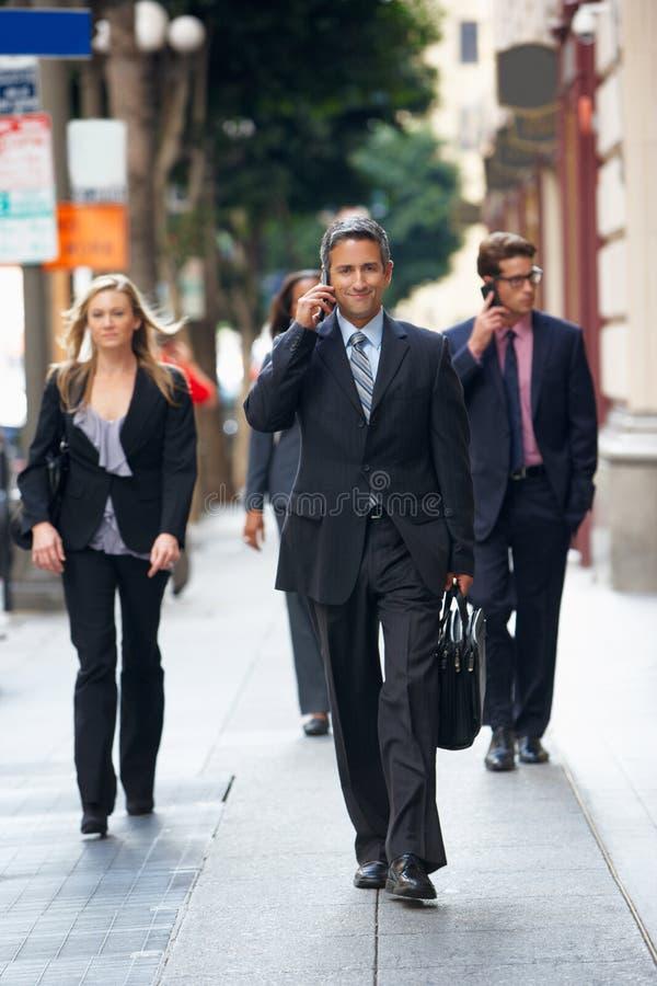 Grupo de empresários que andam ao longo da rua fotografia de stock