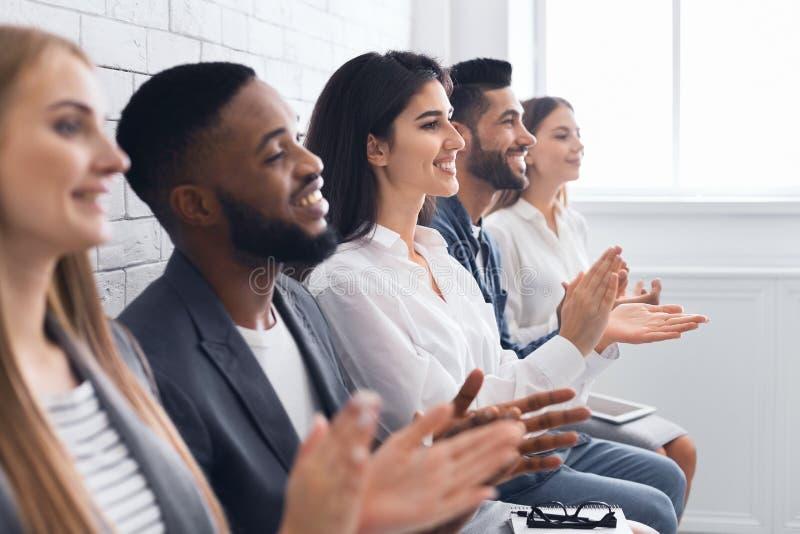 Grupo de empresários que aplaudem as mãos no encontro fotografia de stock