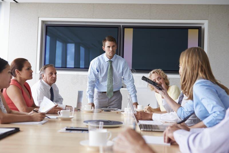 Grupo de empresários que encontram-se em torno da tabela da sala de reuniões fotos de stock