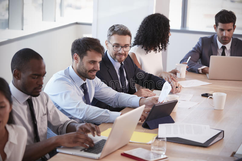 Grupo de empresários que encontram-se em torno da tabela na sala de reuniões imagens de stock royalty free