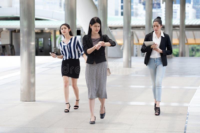 grupo de empresaria joven en la hora punta que camina en la calle y mirar el reloj que comprueba tiempo a atrasado en las calles  foto de archivo libre de regalías