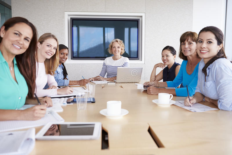 Grupo de empresarias que se encuentran alrededor de la tabla de la sala de reunión imagen de archivo