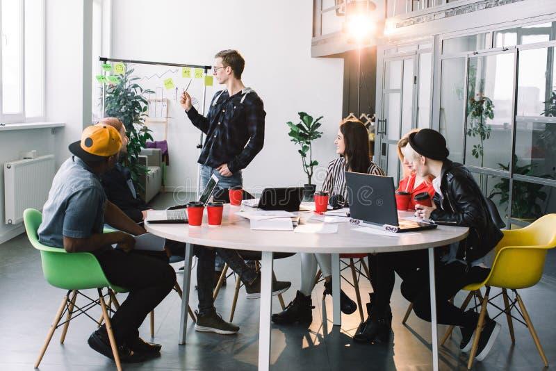 Grupo de empresarios ocasional vestidos que discuten ideas en la oficina Los profesionales creativos recolectaron en la reunión imágenes de archivo libres de regalías