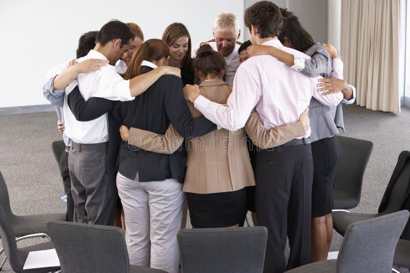 Grupo de empresarios que enlazan en círculo en el seminario de la compañía imagenes de archivo