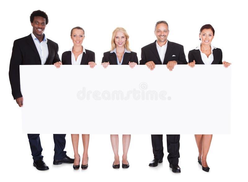 Grupo de empresarios que llevan a cabo el cartel fotografía de archivo