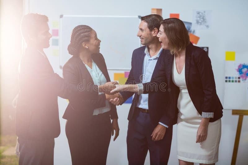 Grupo de empresarios que sacuden las manos con uno a delante de whiteboard foto de archivo libre de regalías