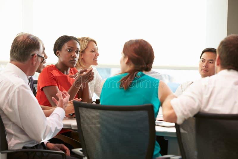 Grupo de empresarios que se encuentran alrededor de la tabla de la sala de reunión imágenes de archivo libres de regalías