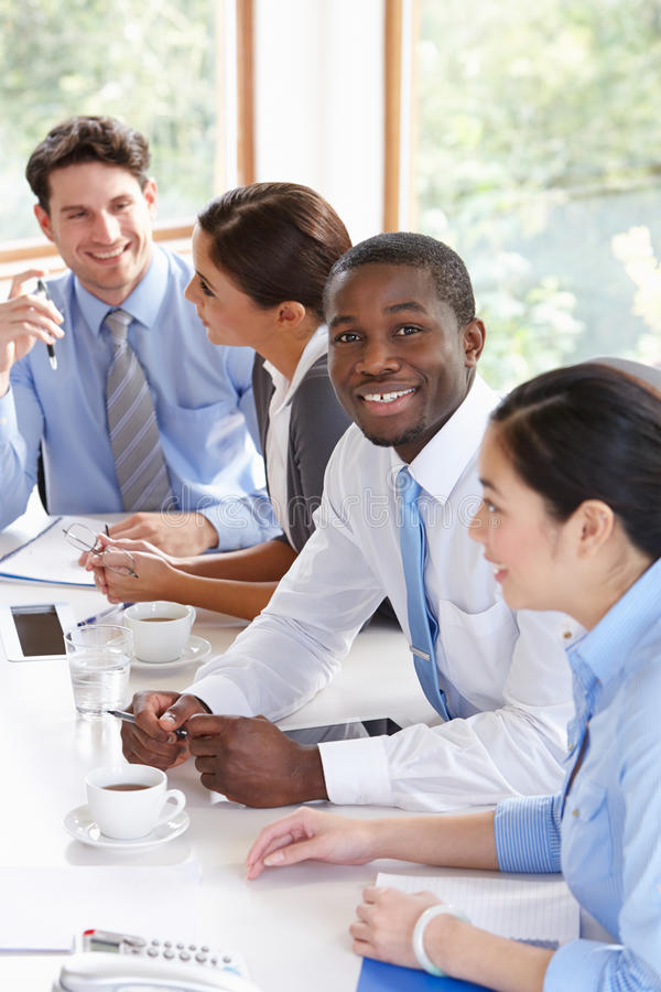 Grupo de empresarios que se encuentran alrededor de la tabla de la sala de reunión fotografía de archivo