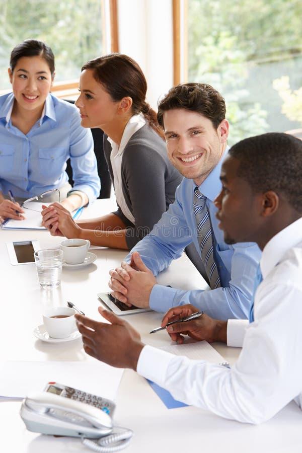 Grupo de empresarios que se encuentran alrededor de la tabla de la sala de reunión imagen de archivo libre de regalías