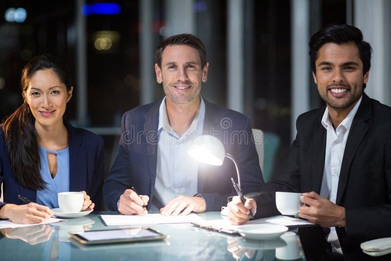 Grupo de empresarios que sonríen en la cámara mientras que comiendo café foto de archivo libre de regalías