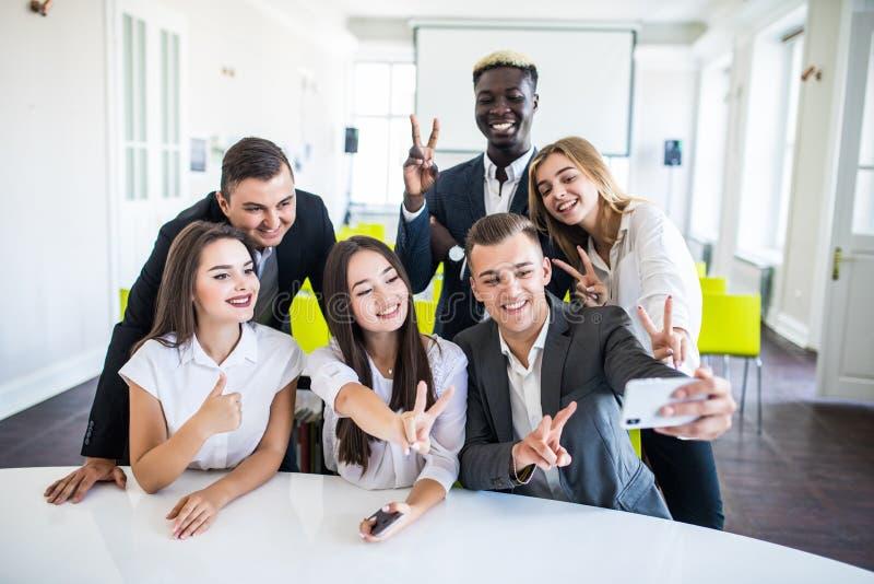 Grupo de empresarios sonrientes felices que hacen el selfie y gesticular Selfie del equipo del negocio fotografía de archivo