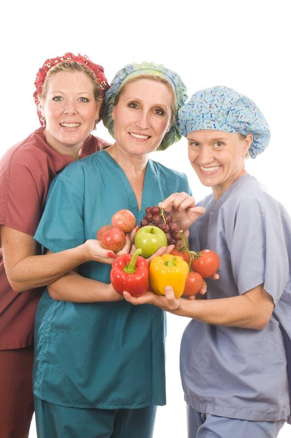 Grupo de enfermeras con las frutas y verdura sanas imagenes de archivo
