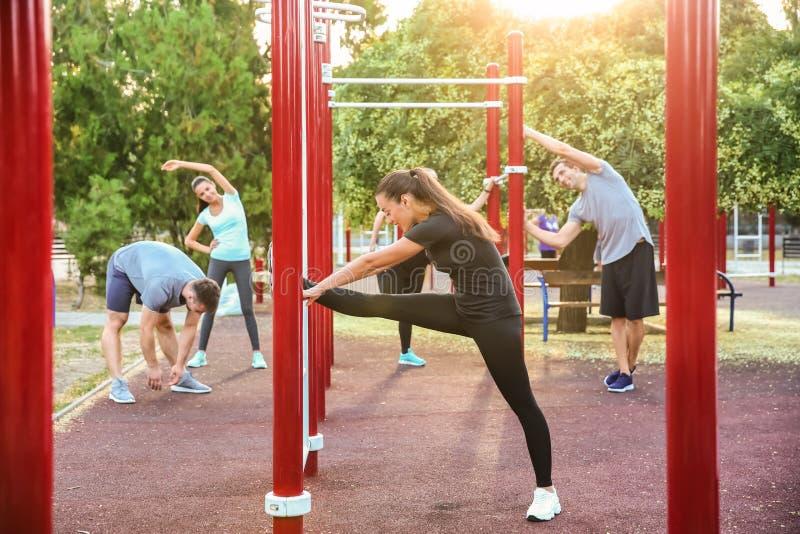 Grupo de entrenamiento deportivo de la gente en campo atlético al aire libre fotos de archivo