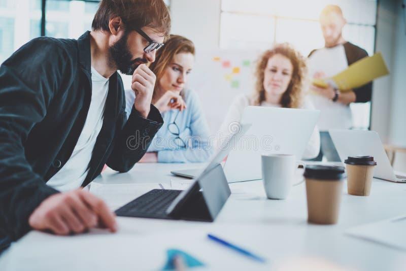 Grupo de equipe nova do negócio que faz a conversação na sala de reunião ensolarada horizontal Fundo borrado fotografia de stock royalty free