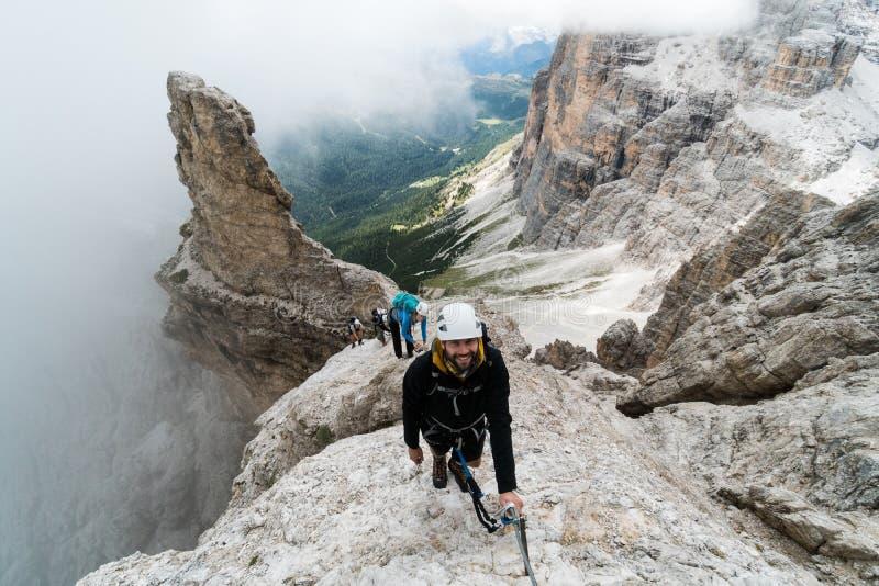 Grupo de escaladores de montaña jovenes en un escarpado vía Ferrata con una vista grandiosa de las dolomías italianas fotos de archivo libres de regalías