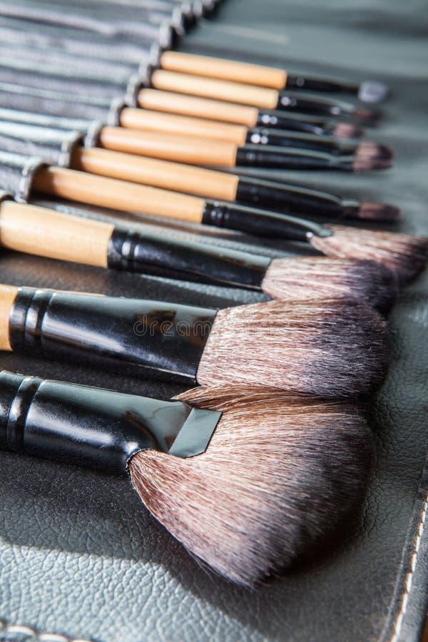 Grupo de escovas da composição no caso da tampa do couro do preto da fileira foto de stock royalty free