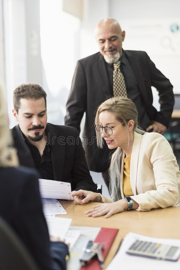 Grupo de escritório do un dos trabalhadores que olha papéis imagens de stock royalty free