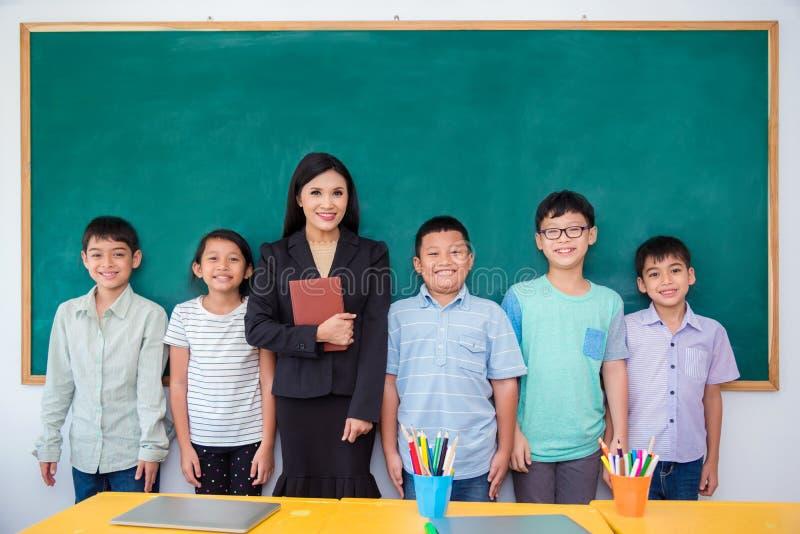 Grupo de estudante e de professor que estão na sala de aula foto de stock