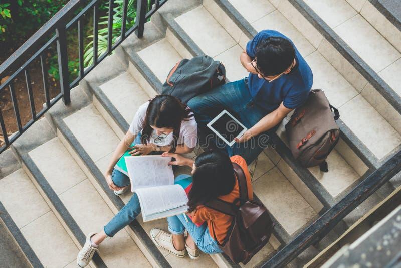 Grupo de estudante universit?rio asi?tica que usa a tabuleta e o telefone celular fora da sala de aula Felicidade e educa??o que  foto de stock royalty free