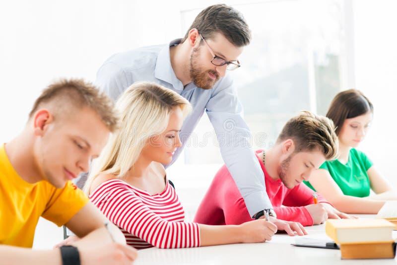Grupo de estudantes adolescentes que estudam na lição na sala de aula fotos de stock royalty free