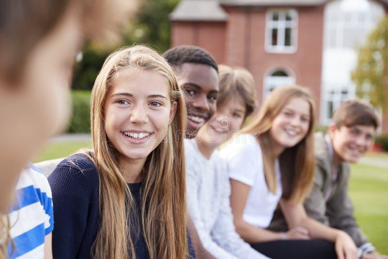 Grupo de estudantes adolescentes que sentam-se fora dos prédios da escola fotos de stock
