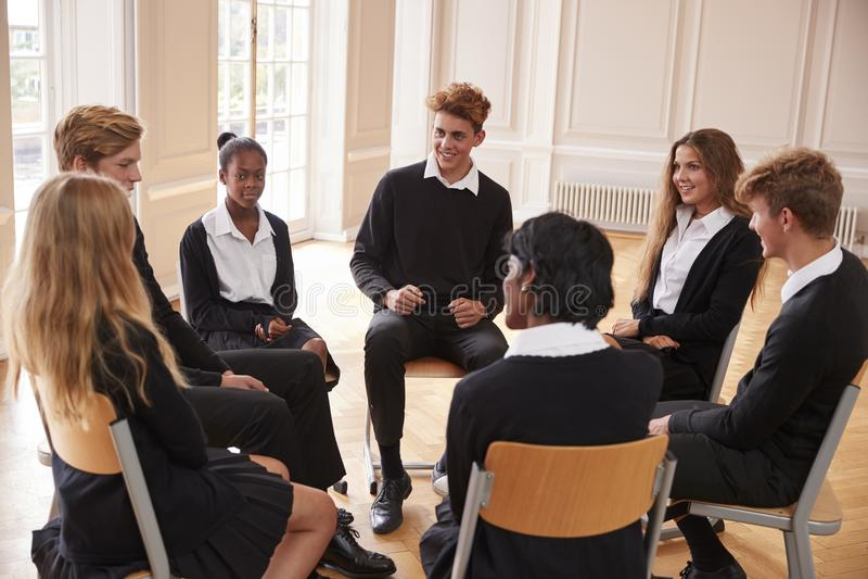 Grupo de estudantes adolescentes que têm a discussão na classe junto fotos de stock royalty free