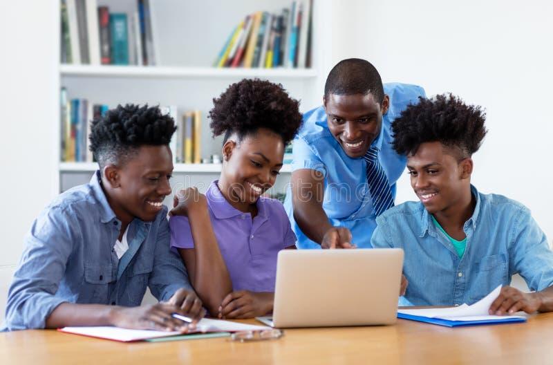 Grupo de estudantes afro-americanos com professor masculino foto de stock royalty free