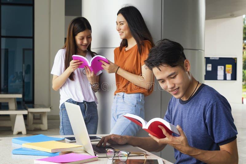 Grupo de estudantes asiáticos da universidade que têm o divertimento fora, utilização do homem foto de stock