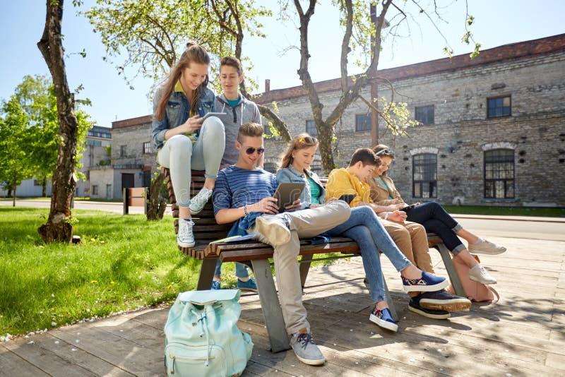 Grupo de estudantes com o PC da tabuleta na jarda de escola fotografia de stock