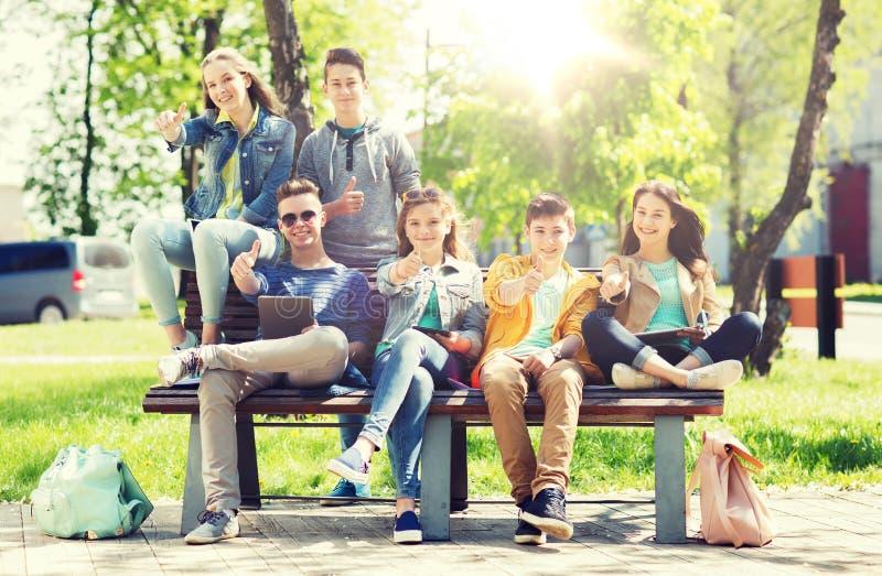 Grupo de estudantes com o PC da tabuleta na jarda de escola foto de stock royalty free