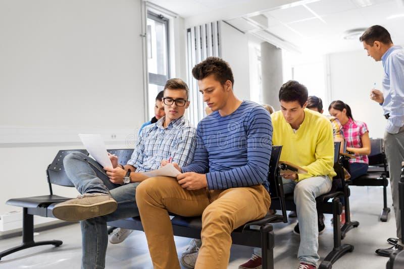 Grupo de estudantes com papéis no salão de leitura imagem de stock royalty free