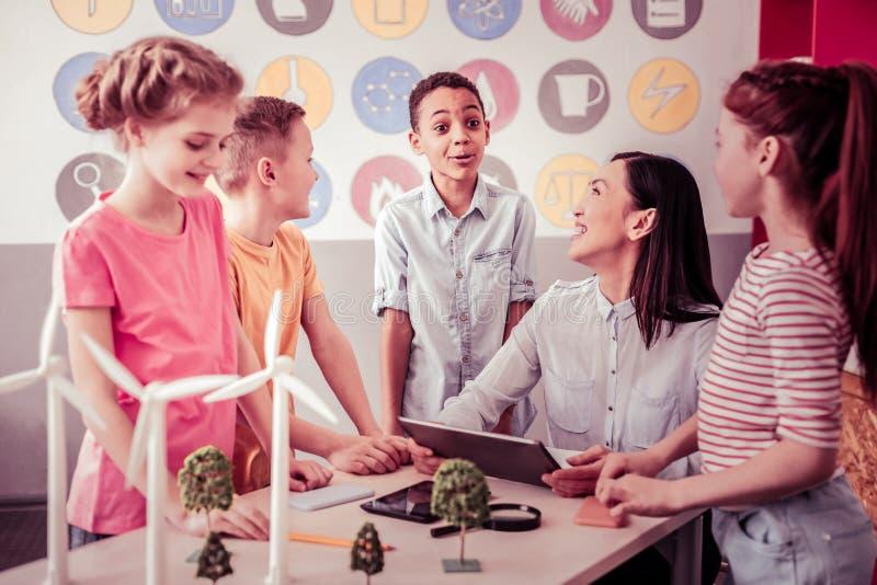 Grupo de estudantes com seu professor que discute situações interessantes imagens de stock royalty free