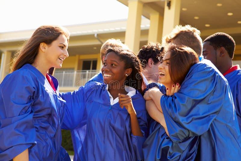 Grupo de estudantes da High School que comemoram a graduação fotografia de stock royalty free