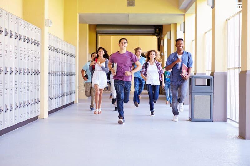 Grupo de estudantes da High School que correm no corredor foto de stock