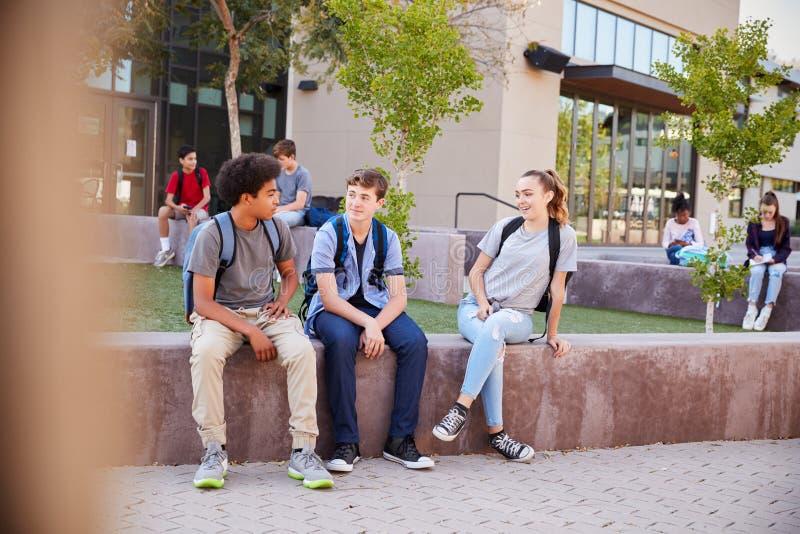 Grupo de estudantes da High School que penduram para fora durante o rebaixo imagem de stock