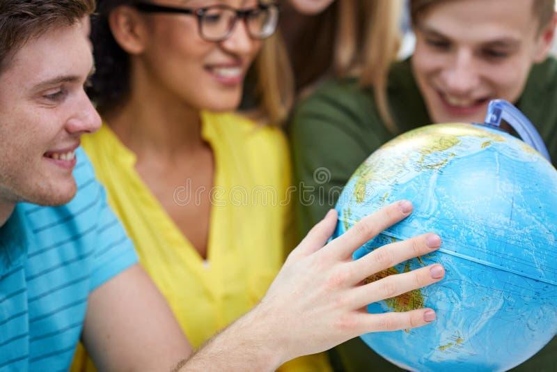 Grupo de estudantes de sorriso que olham o globo imagem de stock