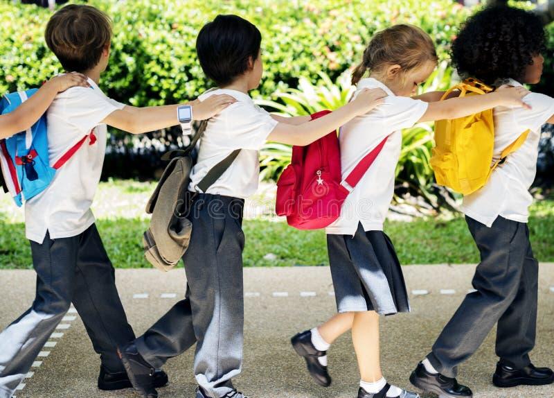 Grupo de estudantes diversos do jardim de infância que andam junto imagens de stock royalty free