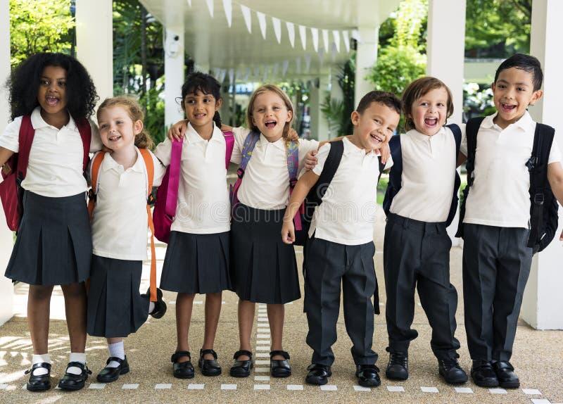 Grupo de estudantes diversos do jardim de infância que estão junto no scho fotografia de stock