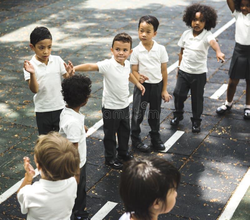 Grupo de estudantes diversos do jardim de infância que estão na linha no playg fotografia de stock