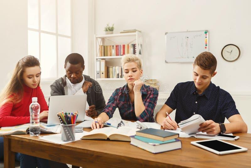 Grupo de estudantes diversos que estudam na tabela de madeira imagens de stock royalty free