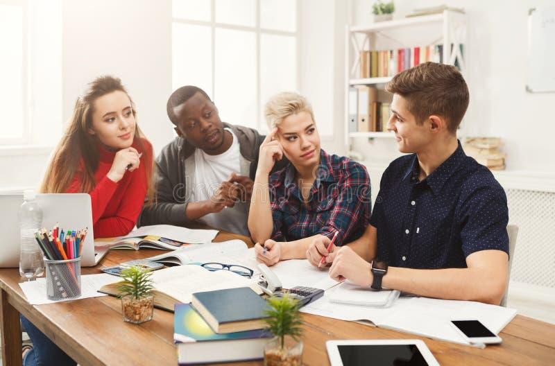 Grupo de estudantes diversos que estudam na tabela de madeira imagens de stock