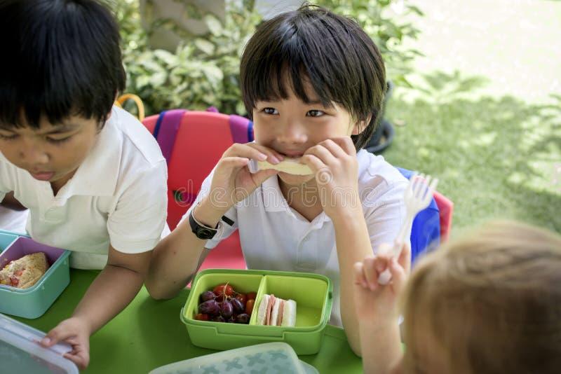 Grupo de estudantes do jardim de infância que comem a pausa para o almoço do alimento junto imagens de stock