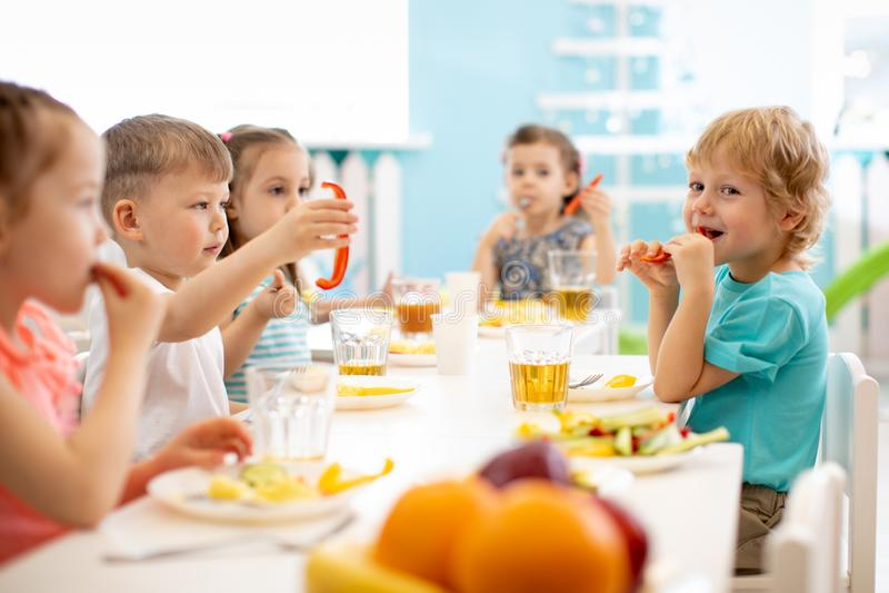 Grupo de estudantes do jardim de infância que comem a pausa para o almoço saudável do alimento junto imagem de stock royalty free