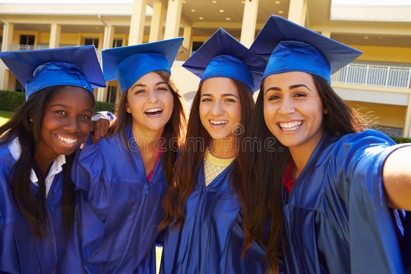 Grupo de estudantes fêmeas da High School que comemoram a graduação imagem de stock