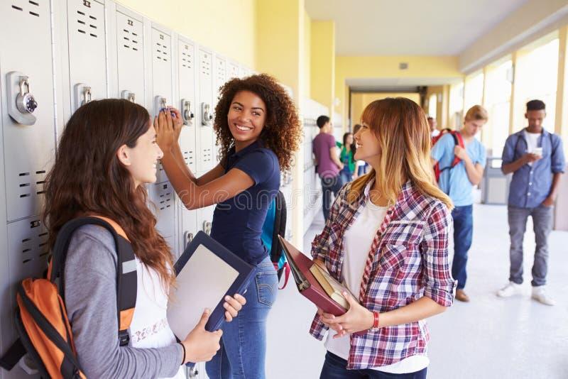 Grupo de estudantes fêmeas da High School que falam por cacifos imagens de stock royalty free