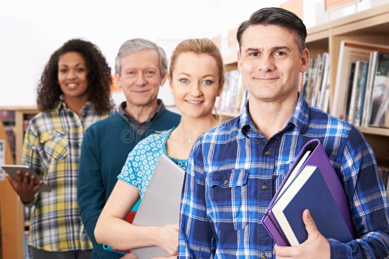 Grupo de estudantes maduros que estudam na biblioteca imagem de stock royalty free