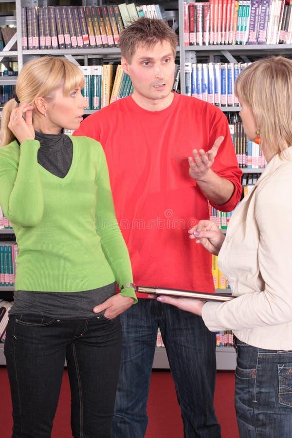 Grupo de estudantes na biblioteca   fotografia de stock